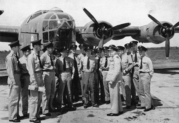 The Commander-in-Chief, Sir Frederick Bowhill, on the right in front, is giving the Liberator crews their final briefing before they take off for Africa.