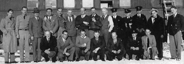 Aircrew from the first Hudson deliveries, Gander, 1940, in front of one of the railway coaches used for sleeping, eating, and offices: Standing, L-R, W.M. King, J.C. Mackey, Snailham, D.J. Dugan, Unidentified, H. Carveth, H.A. Sweet, F. Pearce, A. Gilhousen, H.F. Parker, G.P.M. Eves, D. Anderson, J. Silverthorne, R.H. Page. Kneeling, L-R, A. Finch, J.D. Bledsoe, G.J. Byars, J.R. Fraser, D. Raine, J. Howard, F.G. Godfrey.